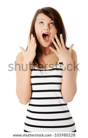 Surprised young woman screaming in excitement and showing hands and all fingers. Long-hair brunette with eyes upward and open mouth wearing striped, black and white top. Isolated on white background. - stock photo