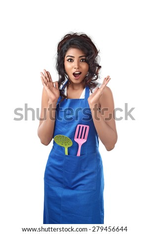 surprised young woman wearing kitchen apron against white background - stock photo