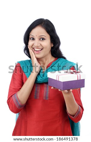 Surprised young woman with gift box against white background - stock photo