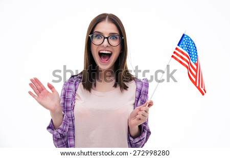 Surprised young woman with glasses holding US flag and screaming over white background. Looking at camera - stock photo