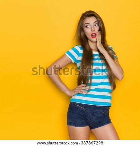 Surprised young woman with long brown hair, blue striped shirt and jeans shorts looking at copy space and holding hand on chin. Three quarter length studio shot on yellow background. - stock photo
