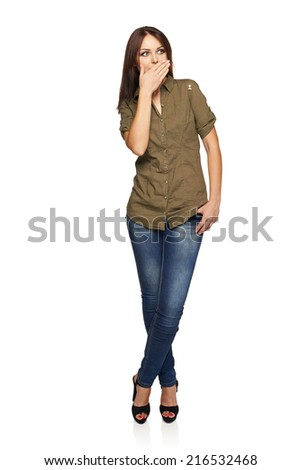 Surprised young woman with mouth covered by palm, standing in full length, looking to the side, over white background - stock photo