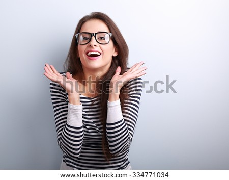 Surprising excited young woman with open mouth gesturing the hands on blue background with empty copy space - stock photo