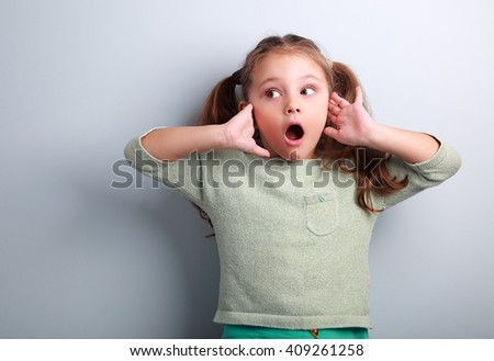 Surprising kid girl with long hair with opened mouth and hand near face looking on blue copy space background