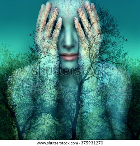 Surreal and artistic image of a girl who covers her eyes with her hands on a background of trees and sky - stock photo