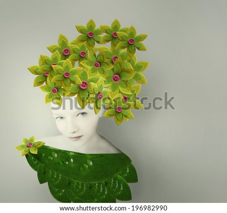 Surreal artistic portrait of a young woman with a bizarre headdress and costume made of leaves and flower fabric - stock photo