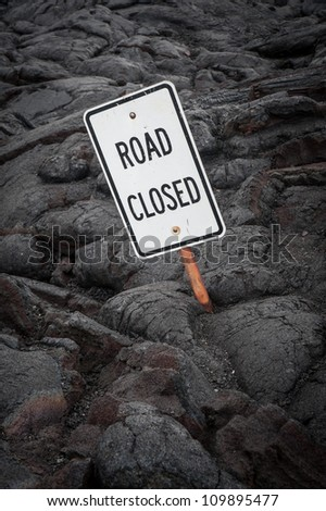 Surreal image of a road closed sign that has been partially covered from a lava flow