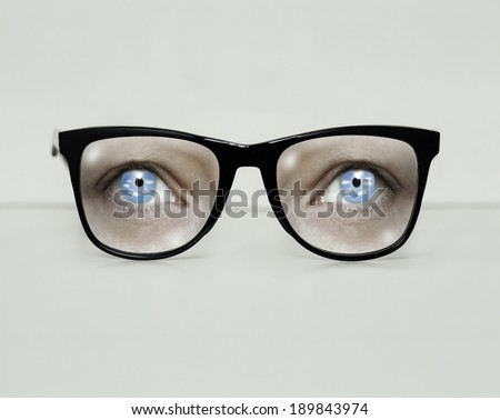 Surreal imagine with a modern black eyeglasses with clouds in the iris of the eyes in gray background - stock photo