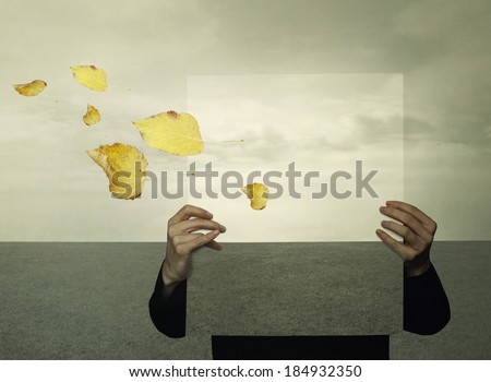 Surreal landscape with a person who holds a framework with the same landscape in the background like an optical effect and leaves in the wind - stock photo