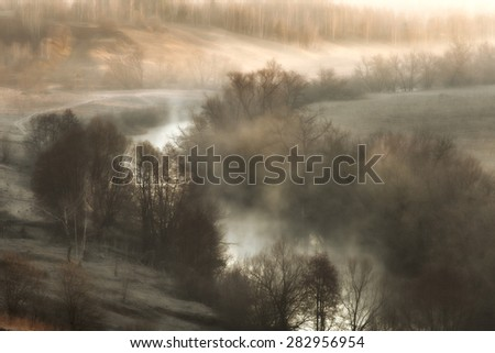 Surreal landscape with a river mist at sunrise in the early spring - stock photo