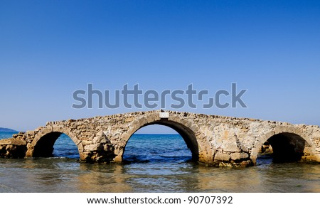 Surreal sea bridge. River dried, sea changed its coastline and the bridge's ruin is located in the middle of water. Argasi, Zakynthos
