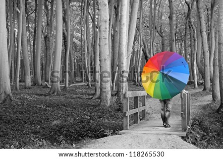 surreal - woman with colorful umbrella in the woods - stock photo