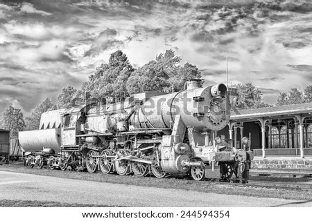 Surrealistic monochrome old steam locomotive on station platform. Dramatic cloudy sky background. - stock photo