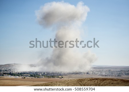 Suruc, Turkey - October 22, 2014. Smoke rises in Kobani, Syria, after an airstrike by the U.S.-led coalition, as seen from the top of a hill near Suruc, at the Turkish - Syrian border.