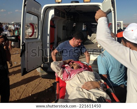 SURUC, TURKEY-SEPTEMBER 20, 2014: Turkey opened its border to Syrians fleeing the town of Kobane in fear of an Islamic State attack. Tens of thousands have fled to Turkey. A view of patient Syrian.  - stock photo