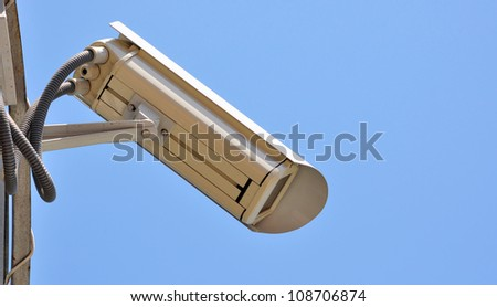 Surveillance cam on sky background watch right - stock photo