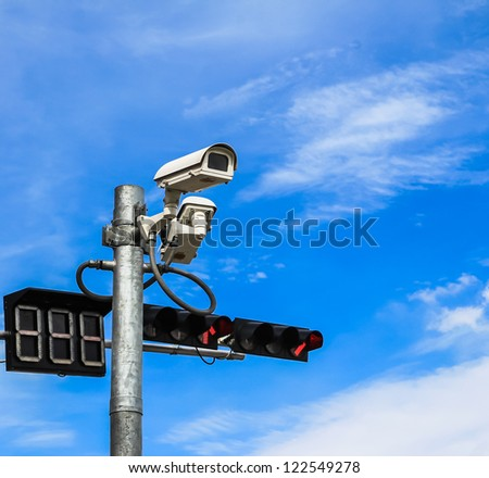 surveillance camera and traffic light against blue sky - stock photo