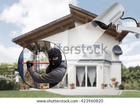 Surveillance Camera Capturing Burglar Using Crowbar To Open Glass Door - stock photo