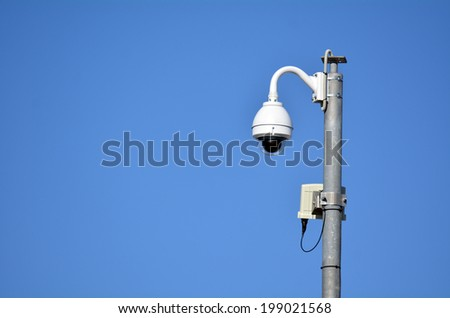 Surveillance camera on a high pole against blue sky. concept photo of modern security and public protection. copyspace - stock photo