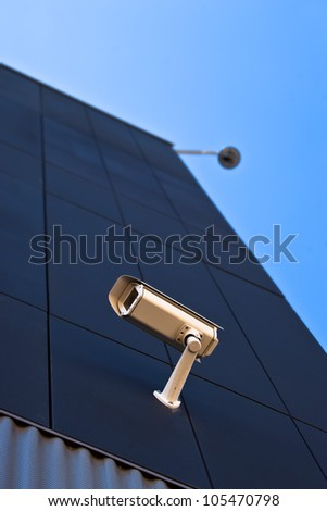 surveillance camera on the wall of a public building - stock photo