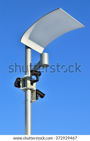 Surveillance cameras and modern lighting fixtures on the lamppost