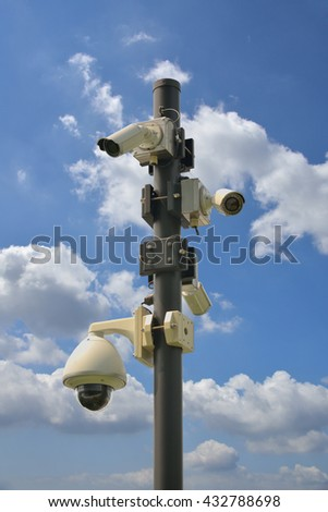 Surveillance cameras on a post on the street against cloudy sky in Yokohama, Japan. There are several security cameras attached to the pole which cover all directions.