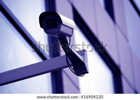 Surveillance, CCTV, security camera installed on a modern building - great for topics like safety, security etc. - stock photo