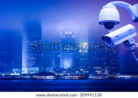 Surveillance Security Camera or CCTV over big city at night - stock photo