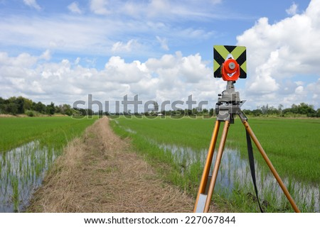 Survey instrument set on a tripod in the field - stock photo