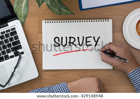 SURVEY man hand notebook and other office equipment such as computer keyboard - stock photo