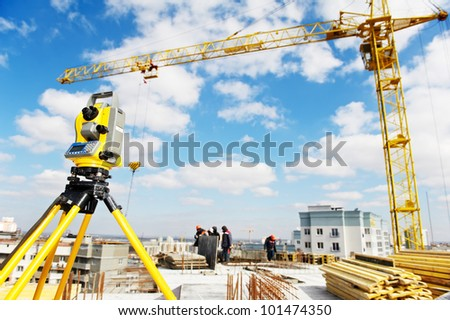 Surveying measuring equipment theodolite transit on tripod at construction building area site - stock photo