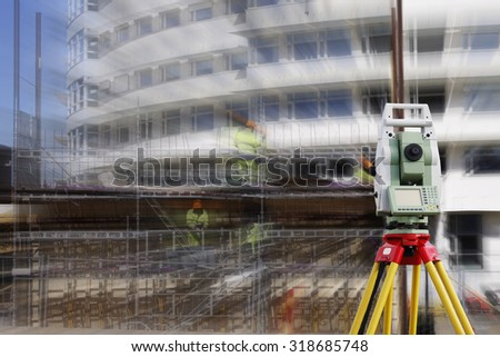 surveying measuring instrument, close-ups,  aimed at building site, zoom effect on background - stock photo