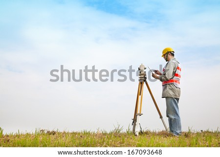 Surveyor engineer making measure on the field with tablet pc - stock photo