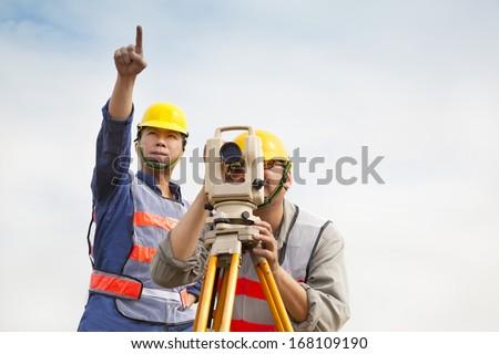 Surveyor engineer making measure with partner  - stock photo