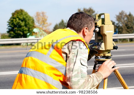 Surveyor engineer making measuring at highway with optical equipment theodolite