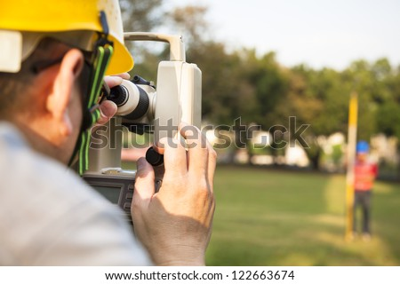 Surveyor engineer with partner making measure on the field - stock photo