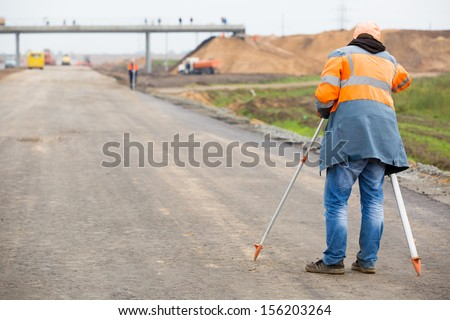 Surveyor engineer worker making measuring with theodolite equipment at construction site during road works