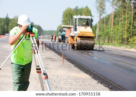 Surveyor engineer worker making measuring with theodolite instrument equipment during construction road works - stock photo