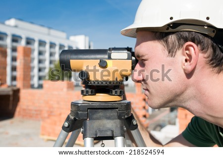 Surveyor engineer worker making measuring with theodolite tool equipment at construction site - stock photo