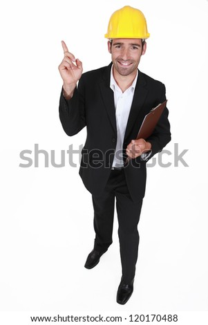 Surveyor holding clip-board and pointing - stock photo