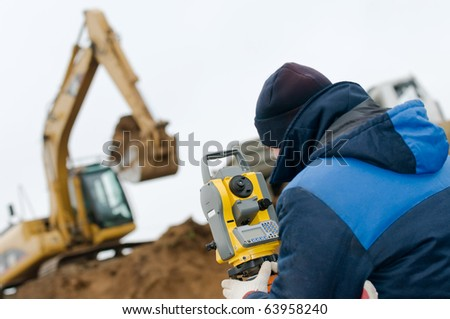 surveyor worker with geodesy equipment device theodolite at land surveying outdoors - stock photo