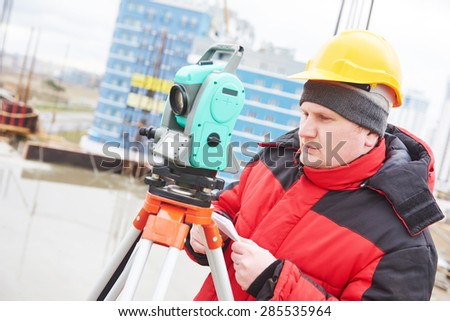 surveyor working with theodolite transit equipment at construction site