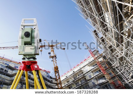 surveyors measuring instrument, close-ups, large super-wide construction site in background - stock photo