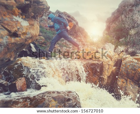 Survival man crossing river in mountains with backpack, sunrise or sunset and danger - stock photo