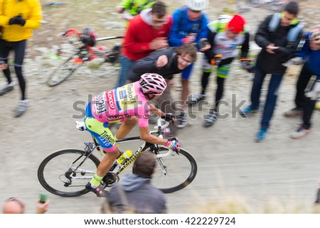 "Susa, Italy - May 30, 2015: Cyclist climbing ""Colle delle Finestre"" mountain pass during the 2015 Giro d'Italia, the international annual bicycle race held in Italy. People supporting the racers."