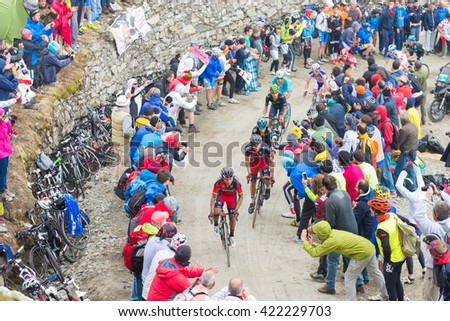 "Susa, Italy - May 30, 2015: Cyclists climbing ""Colle delle Finestre"" mountain pass during the 2015 Giro d'Italia, the international annual bicycle race held in Italy. People supporting the racers."