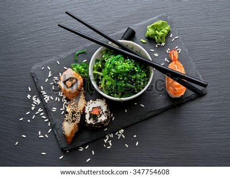 Sushi and seaweed salad on slate table - stock photo
