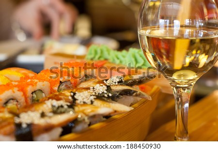 Sushi and white wine on the table - stock photo
