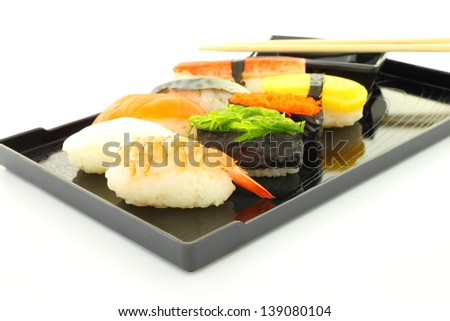 Sushi black rectangle plate focus shrimp on white table.