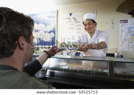 Sushi chef handing sushi to customer in restaurant - stock photo